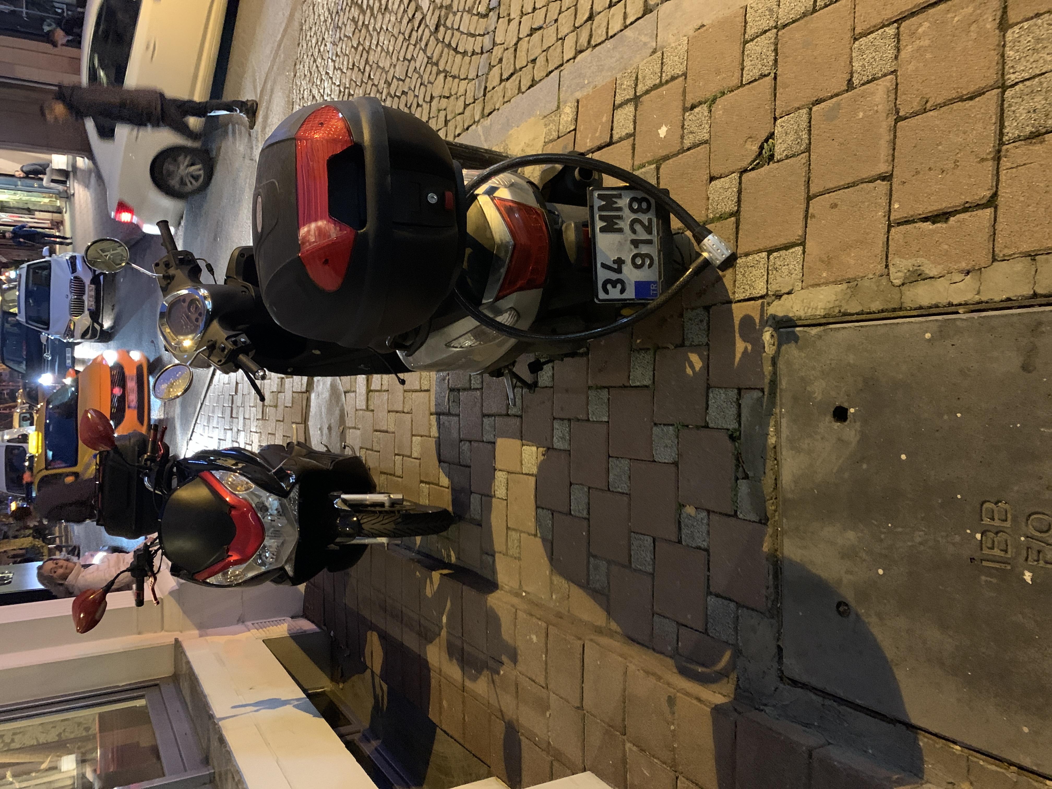 İki motorsiklet kaldırıma park etmiş bütün yolu kaplıyor.